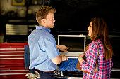 istock Happy customer discusses repairs with auto mechanic. Laptop. 471057846
