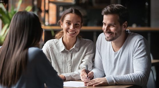 938640610 istock photo Happy customers couple ready to sign loan agreement meeting agent 1199696904