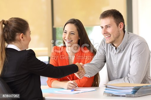 istock Happy customers handshaking after a deal 828447052