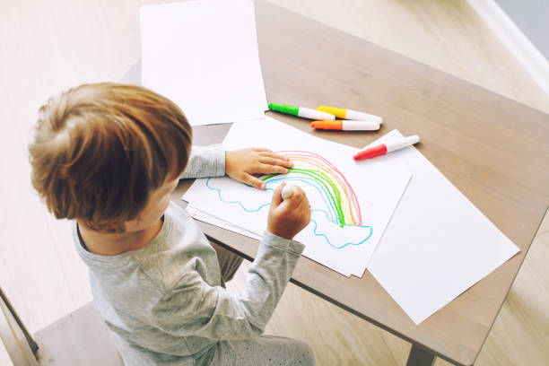 Happy cute and beautiful baby smiling at home drawing at the table in the nursery stock photo