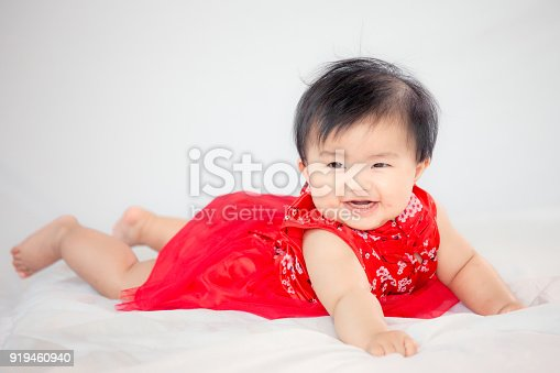 Happy cute asian baby girl in chinese tradition dress smiling and crawling in the bed
