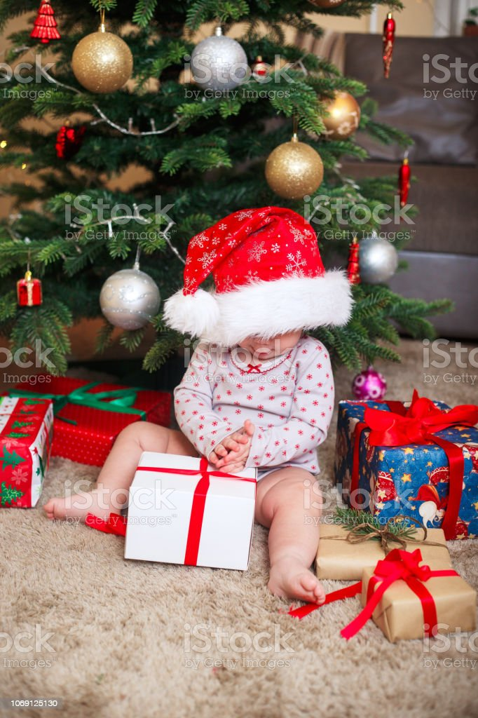 Cute Christmas Gifts For Girlfriend.Happy Cute Baby Girl In Santa Claus Hat Holding Christmas