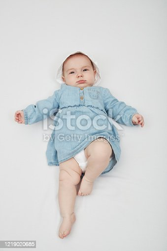 923852236 istock photo Happy cute baby lying on white sheet 1219020685