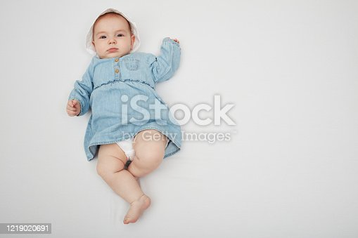 923852236 istock photo Happy cute baby lying on white sheet 1219020691