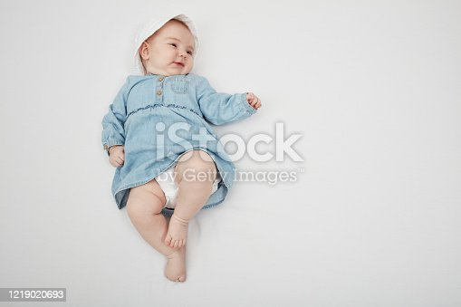 923852236 istock photo Happy cute baby lying on white sheet 1219020693