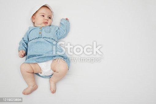 923852236 istock photo Happy cute baby lying on white sheet 1219020694