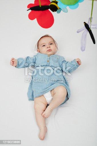 923852236 istock photo Happy cute baby lying on white sheet 1219020695