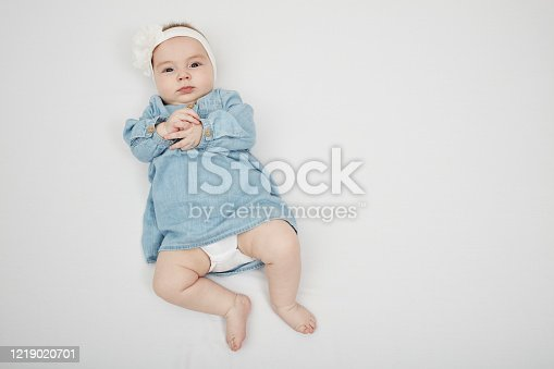 923852236 istock photo Happy cute baby lying on white sheet 1219020701