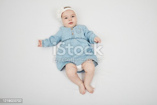 923852236 istock photo Happy cute baby lying on white sheet 1219020702