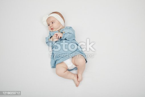 923852236 istock photo Happy cute baby lying on white sheet 1219020712