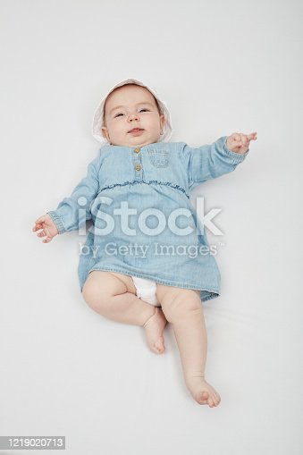 923852236 istock photo Happy cute baby lying on white sheet 1219020713