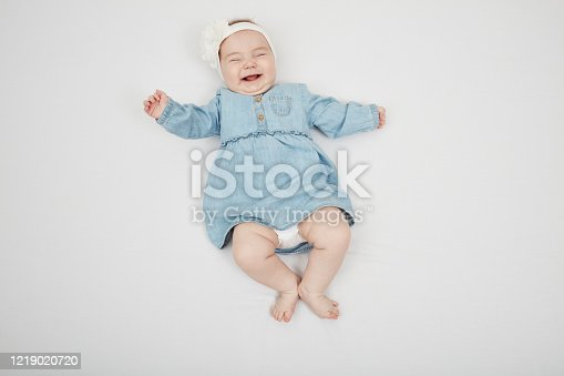 923852236 istock photo Happy cute baby lying on white sheet 1219020720