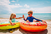 happy cute boy and girl play with floaties on beach vacation
