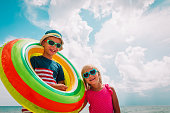 happy cute boy and girl play with floatie on beach vacation