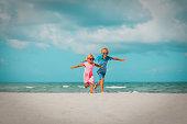happy cute boy and girl run play at beach vacation
