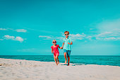 happy cute boy and girl running on beach vacation