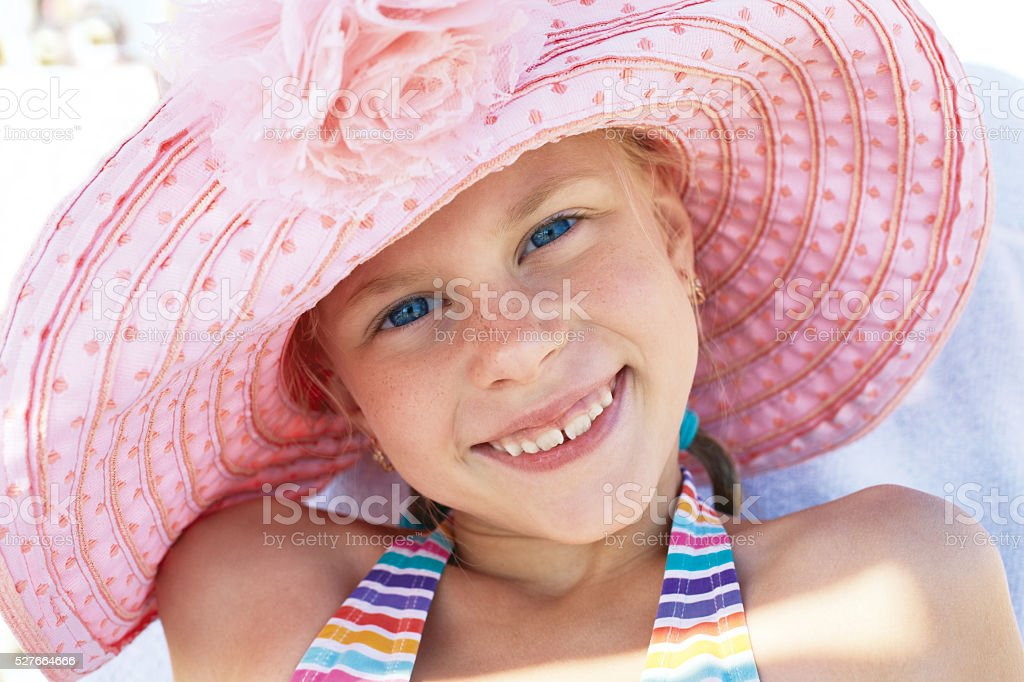 Happy cute child lying down on deckchair of beach resort stock photo
