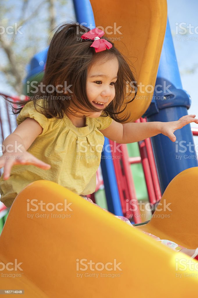 happy cute girl going down slide royalty-free stock photo