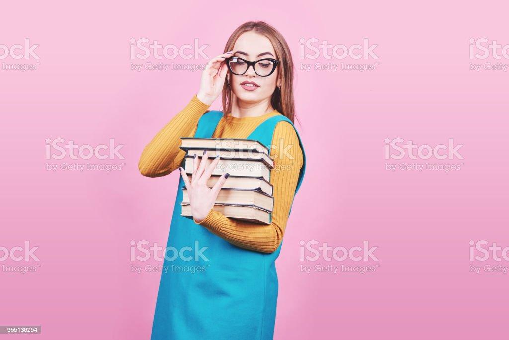 Glücklich niedliche Mädchen in Gläsern in Händen hält, einen Stapel Bücher auf bunte Rosa hintergrund isoliert – Foto