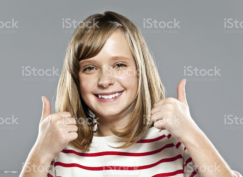 Happy cute girl Portrait of cute girl wearing striped blouse smiling at camera with thumbs up. Studio shot. 10-11 Years Stock Photo