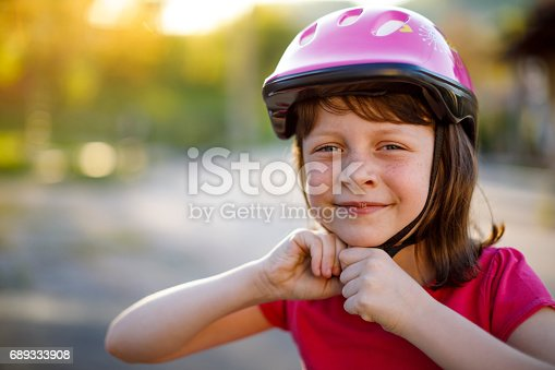 Happy cute girl putting cycle helmet on