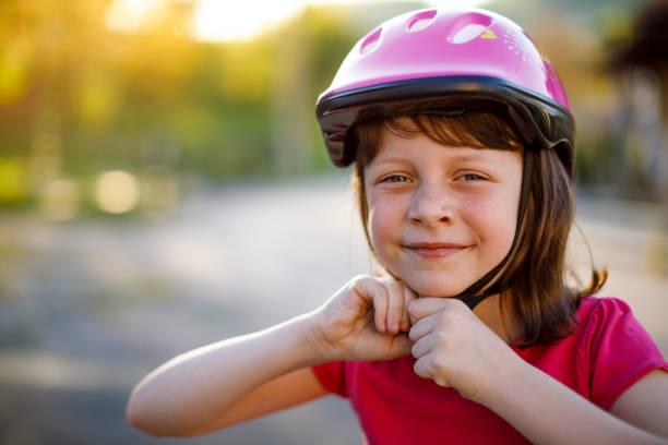 Happy cute girl putting cycle helmet on stock photo