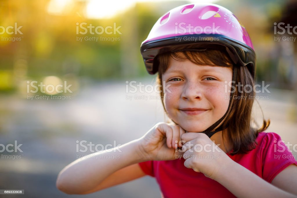 Happy cute girl putting cycle helmet on stock photo