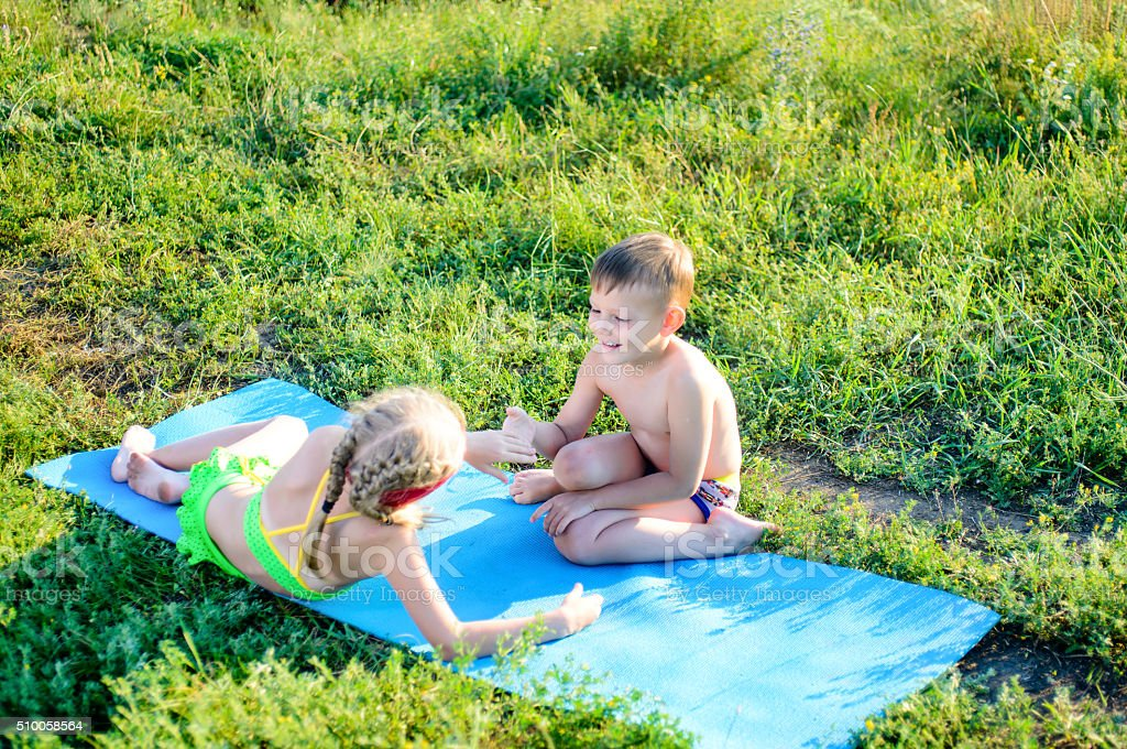 Happy Cute Kids Cuddling on Mat at the Grasses stock photo