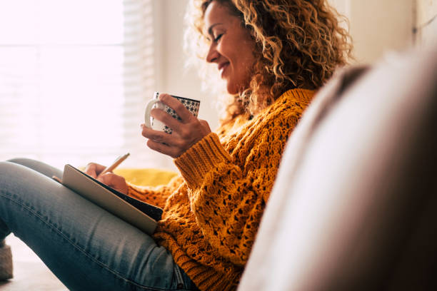 Happy cute lady at home write notes on a diary while drink a cup of tea and rest and relax taking a break. autumn colors and people enjoying home lifestyle writing messages or lists. Blonde curly beautiful lady sit down in the house stock photo