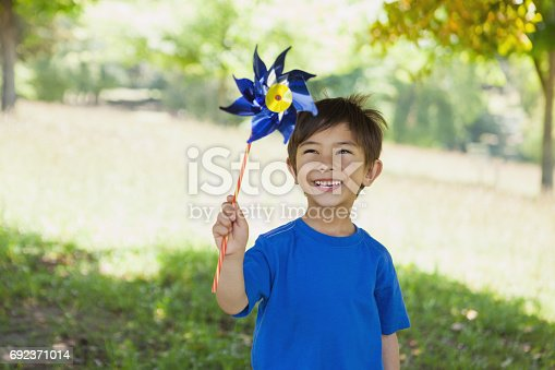 istock Happy cute little boy holding pinwheel at park 692371014