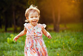 Happy cute little girl running on the grass in the park. Happiness