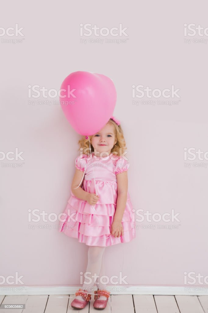 Happy Cute Little Girl With Pink Balloon Heart On A Pink Background