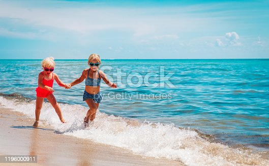 happy cute little girls play with waves on beach, kids enjoy vacation at sea