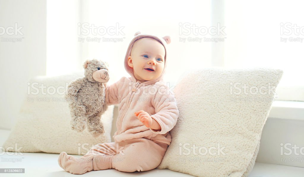 Happy cute smiling baby with teddy bear toy home stock photo