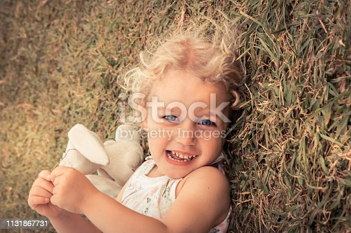 istock Happy cute smiling child girl with beautiful eyes lying on grass concept happiness carefree childhood lifestyle 1131867731