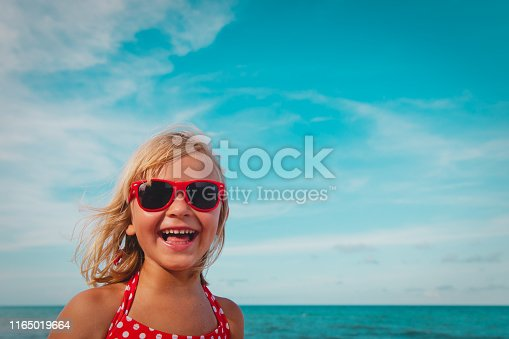 604367022 istock photo happy cute smiling girl at summer beach 1165019664