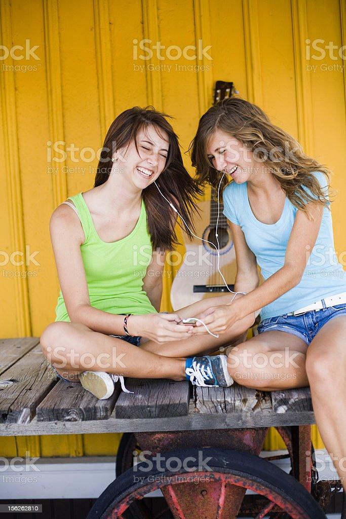 Happy cute  teenage girls listening to music royalty-free stock photo