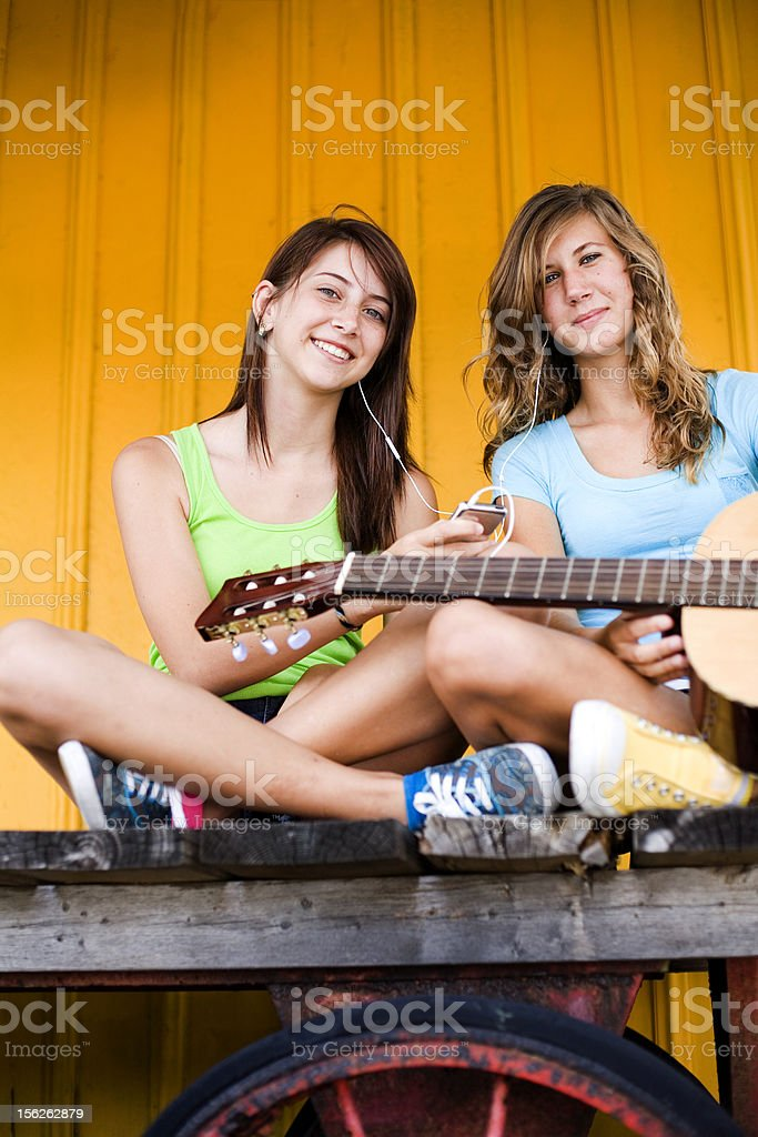 Happy cute  teenage girls listening to music royalty-free stock photo