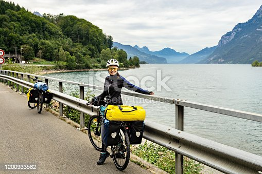 Woman bicycle traveler is posing on background of  mountains and lake during bike trip. Walensee, Switzerland, Europe.
