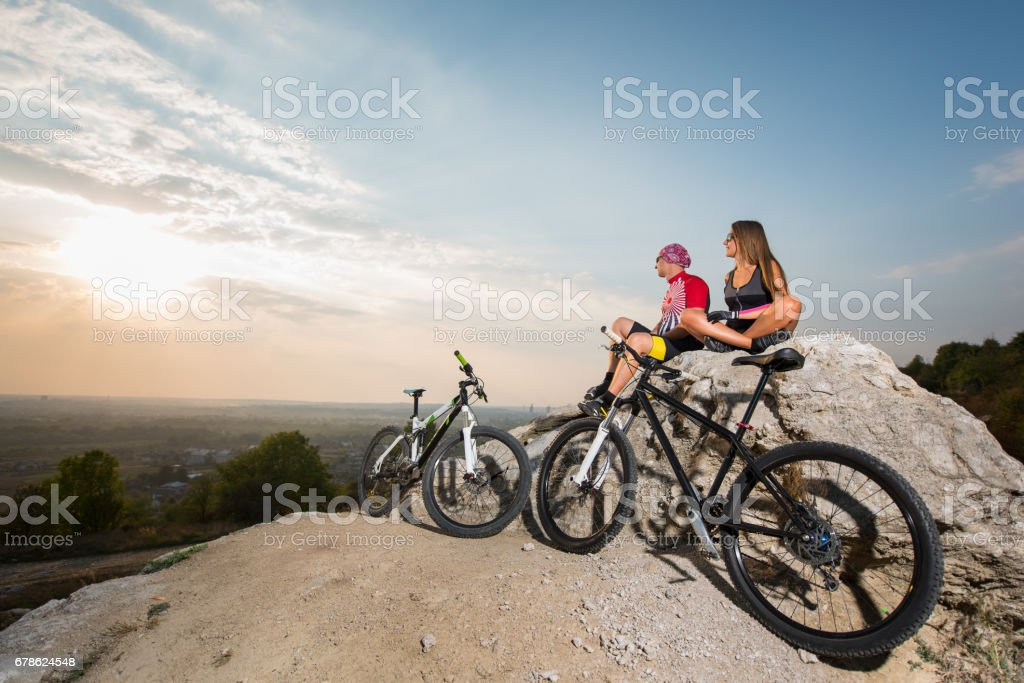 Casal feliz ciclista em óculos de sol sentado numa rocha - foto de acervo
