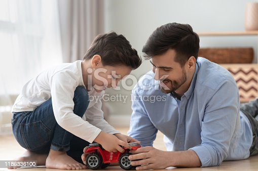 540396126istockphoto Happy dad and kid son play toy car at home 1186336100