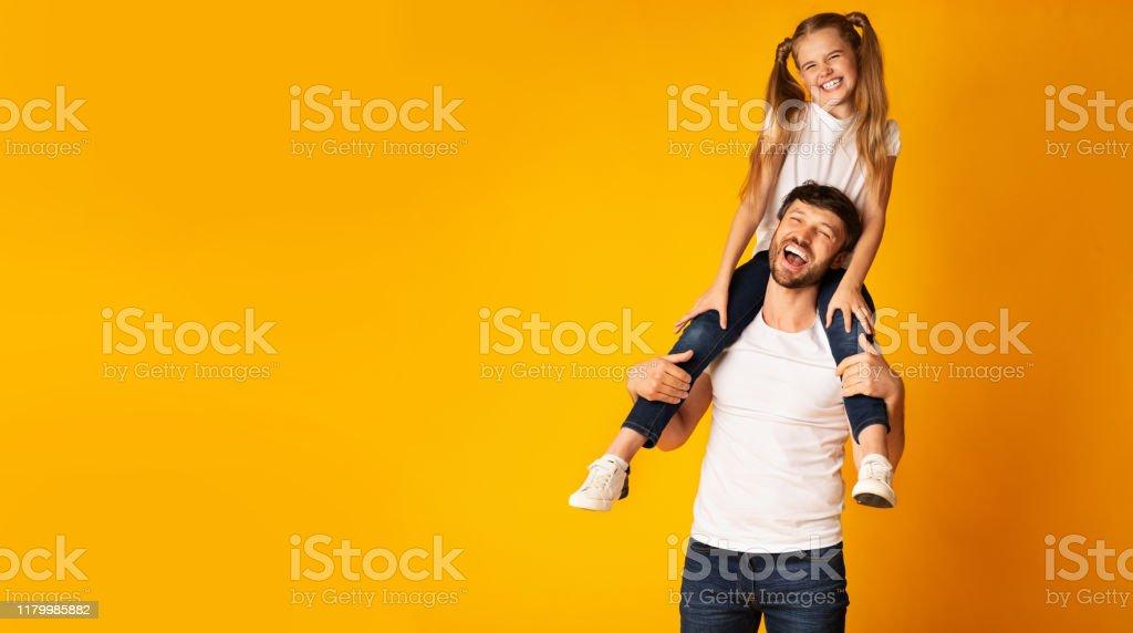 Glücklicher Vater tragen Tochter auf Schultern auf gelbem Hintergrund, Panorama - Lizenzfrei Alleinerzieher Stock-Foto