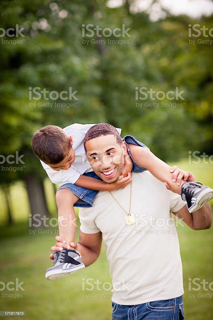 Happy Dad Carrying Son on His Shoulders Outside - Stock image .