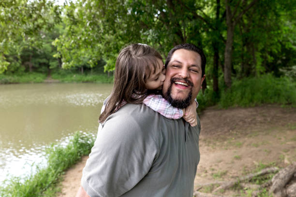 Happy dad spends the day outdoors with his daughter Happy Hispanic man smiles as his young daughter kisses his cheek. little girl kissing dad on cheek stock pictures, royalty-free photos & images
