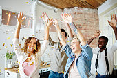 Ecstatic young friends with raised hands having fun and dancing at home
