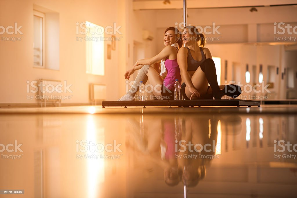 Happy dancers communicating on a break in dance studio. stock photo
