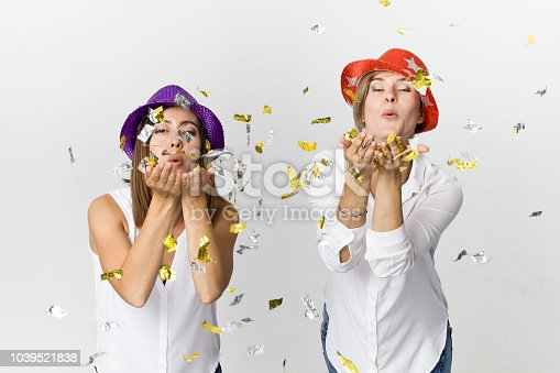 627933752istockphoto Happy dancing young female friends smiling with confetti against white background. Celebrating 1039521838