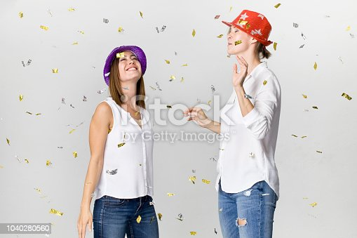 627933752istockphoto Happy dancing young female friends smiling with confetti against white background. Celebrating 1040280560