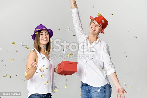 627933752istockphoto Happy dancing young female friends smiling with gift and confetti against white background. Celebrating 1040984874