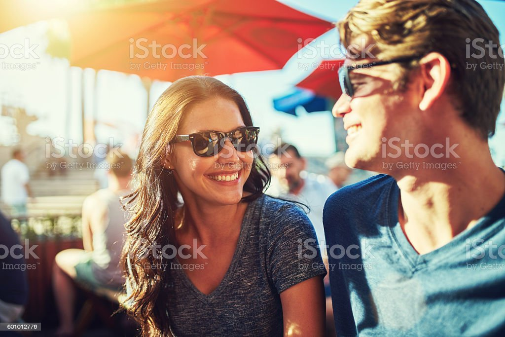 happy dating couple at outdoor restaurant with lens flare stock photo